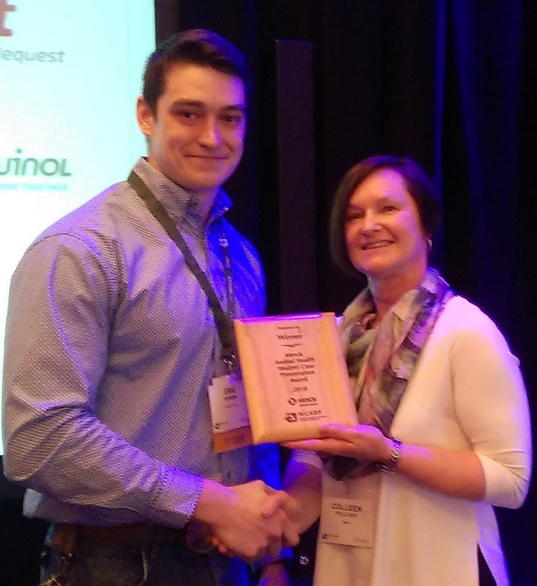 Erik Burows accepts the winning award from Dr. Colleen Pollock (Merck Animal Health)
